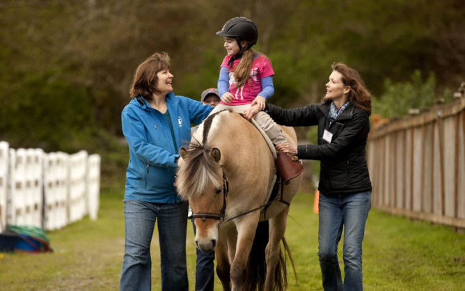 A girl with cerebral palsy participates in hippotherapy, which a new review of research finds has a range of potential therapeutic benefits. (Erika Schultz/The Seattle Times/TNS)